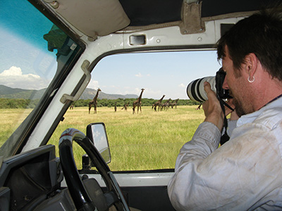 Derek Lee '94 taking photos of giraffes from van